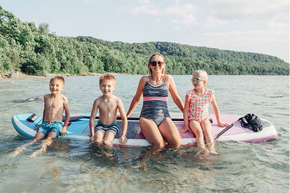 Family on an inflatable paddle board that was constructed by drop stitch welding